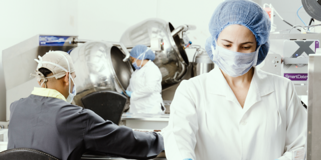 Food safety - people inside factory wearing masks ad coats